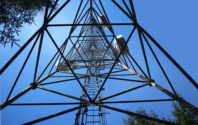 A cell phone tower looking up from inside to a blue sky