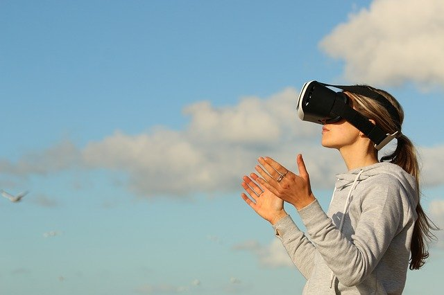 Woman wearing VR headset looking at the sky.
