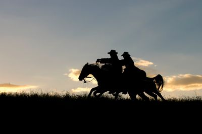 Cowboys at dawn crossing the range