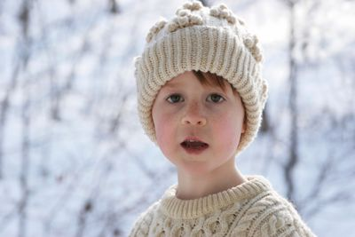 Boy with wool hat and jumper on snowy day